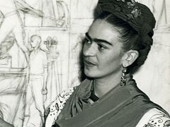 Frida Kahlo in front of a sketch of the Pan-American Unity murals